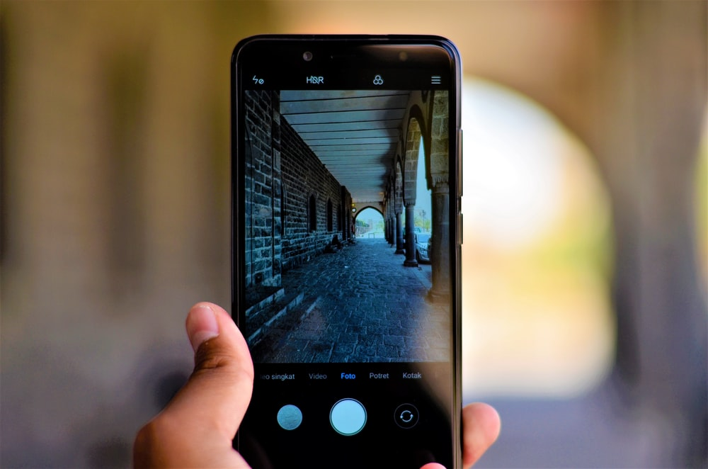 person holding smartphone in shallow photography
