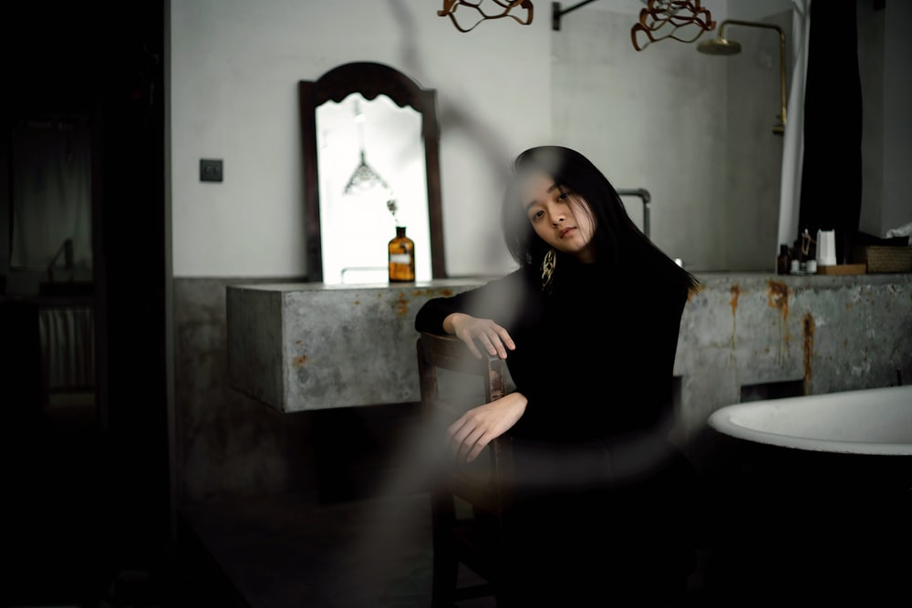 woman sitting on brown chair beside brown glass bottle inside house