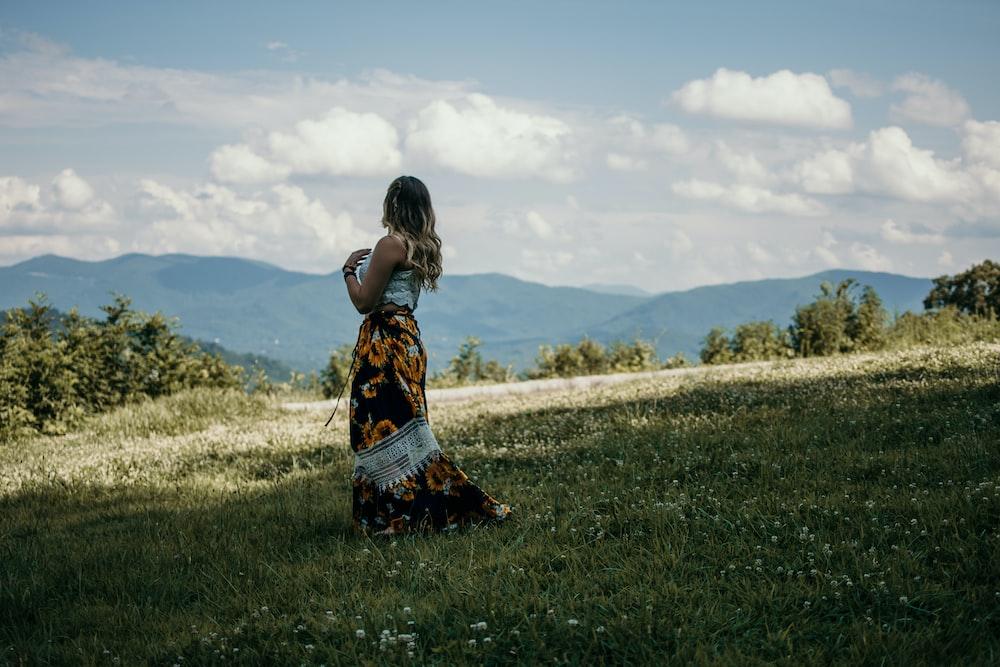 woman standing on green grass field facing mountains