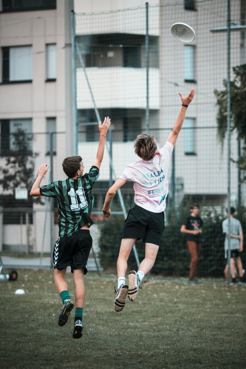 two men reaching frisbee while jumping