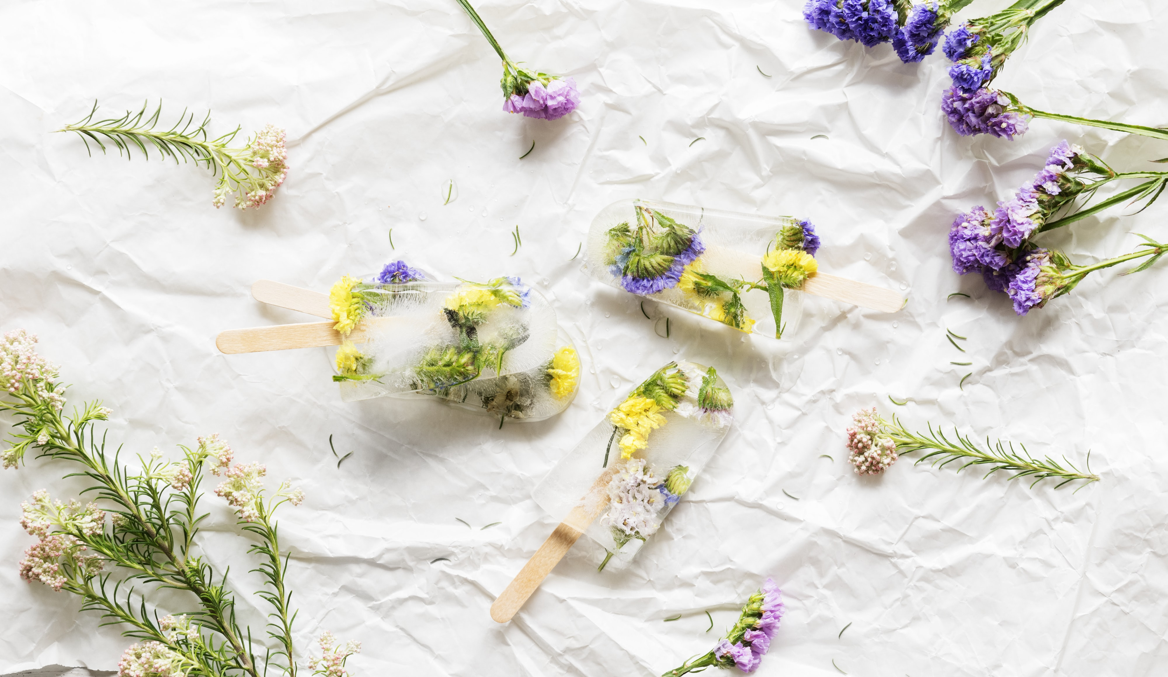 assorted-color flowers lying on white textile
