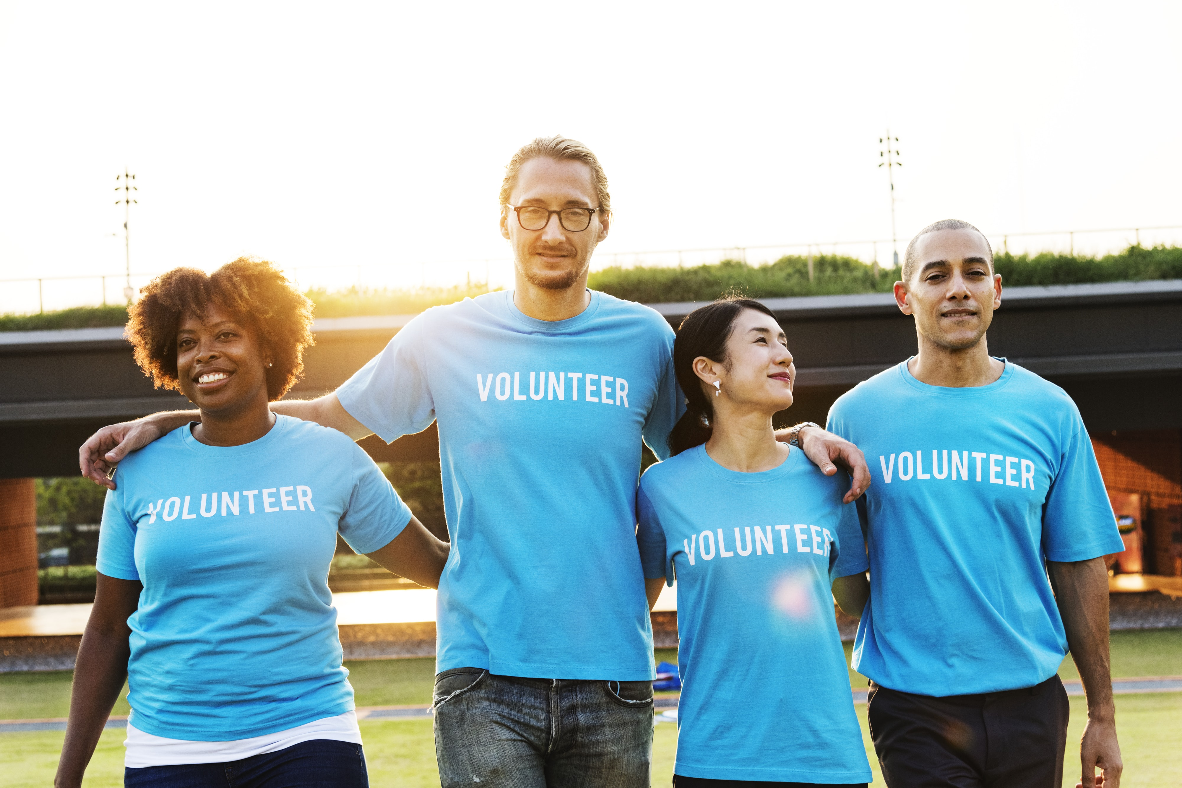two men and women wearing blue volunteer-printed crew-neck t-shirts