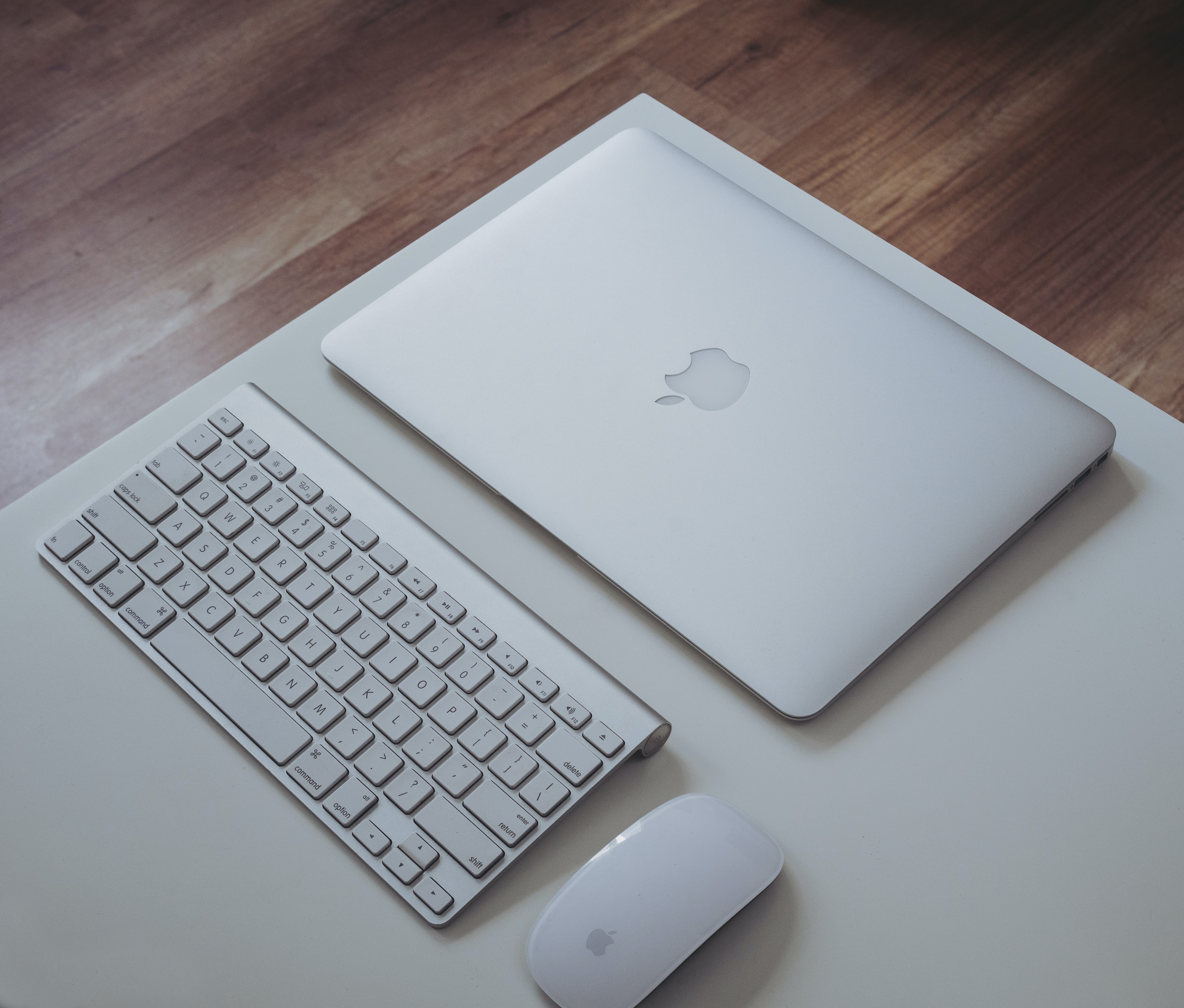 silver MacBook near Apple Magic Keyboard and Apple Magic Mouse on white surface