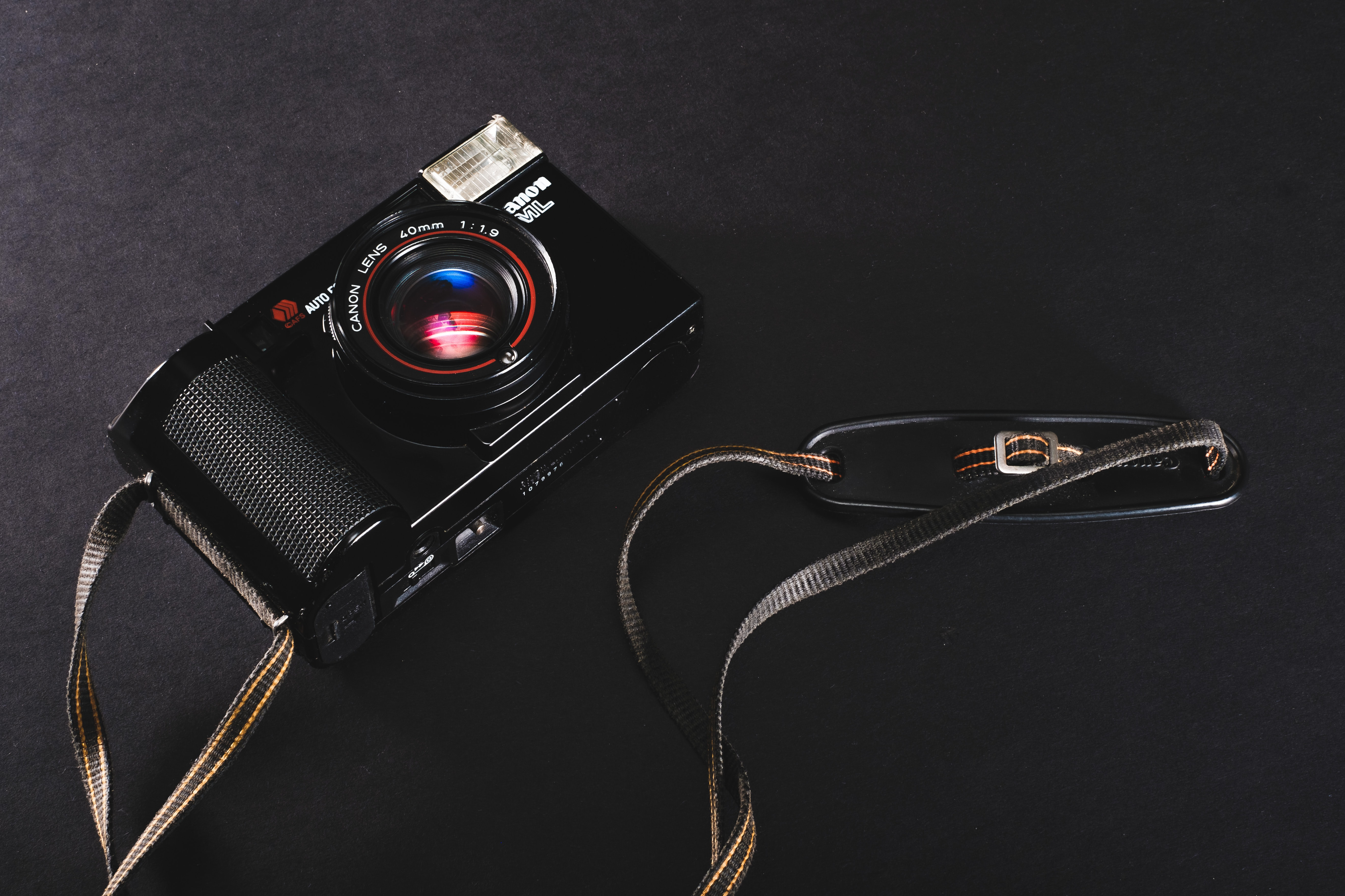 black and red compact camera on black surface