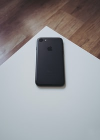 black iPhone 7 on white wooden table