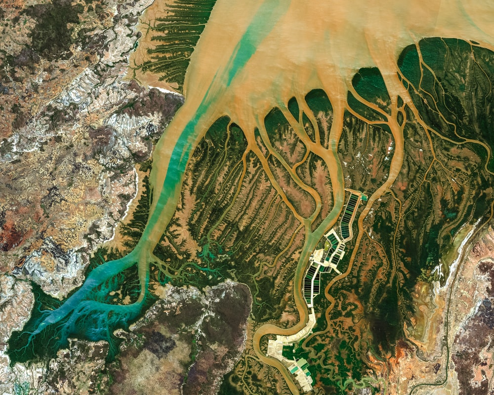 aerial photography of body of water surrounded by rock formation