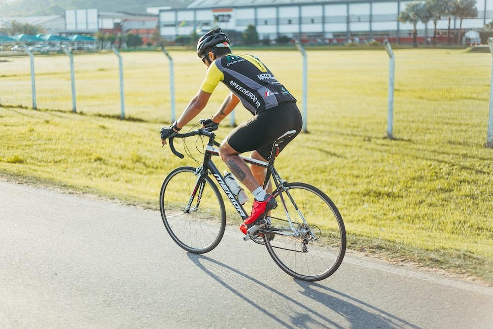 man riding on road bike near fence
