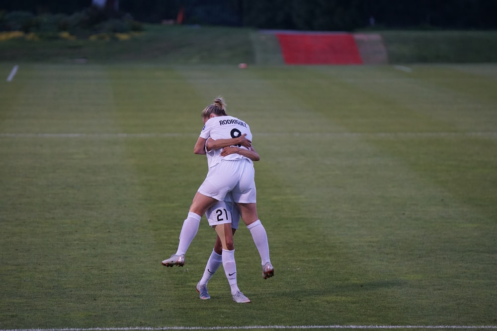 woman hugging her co player on green field