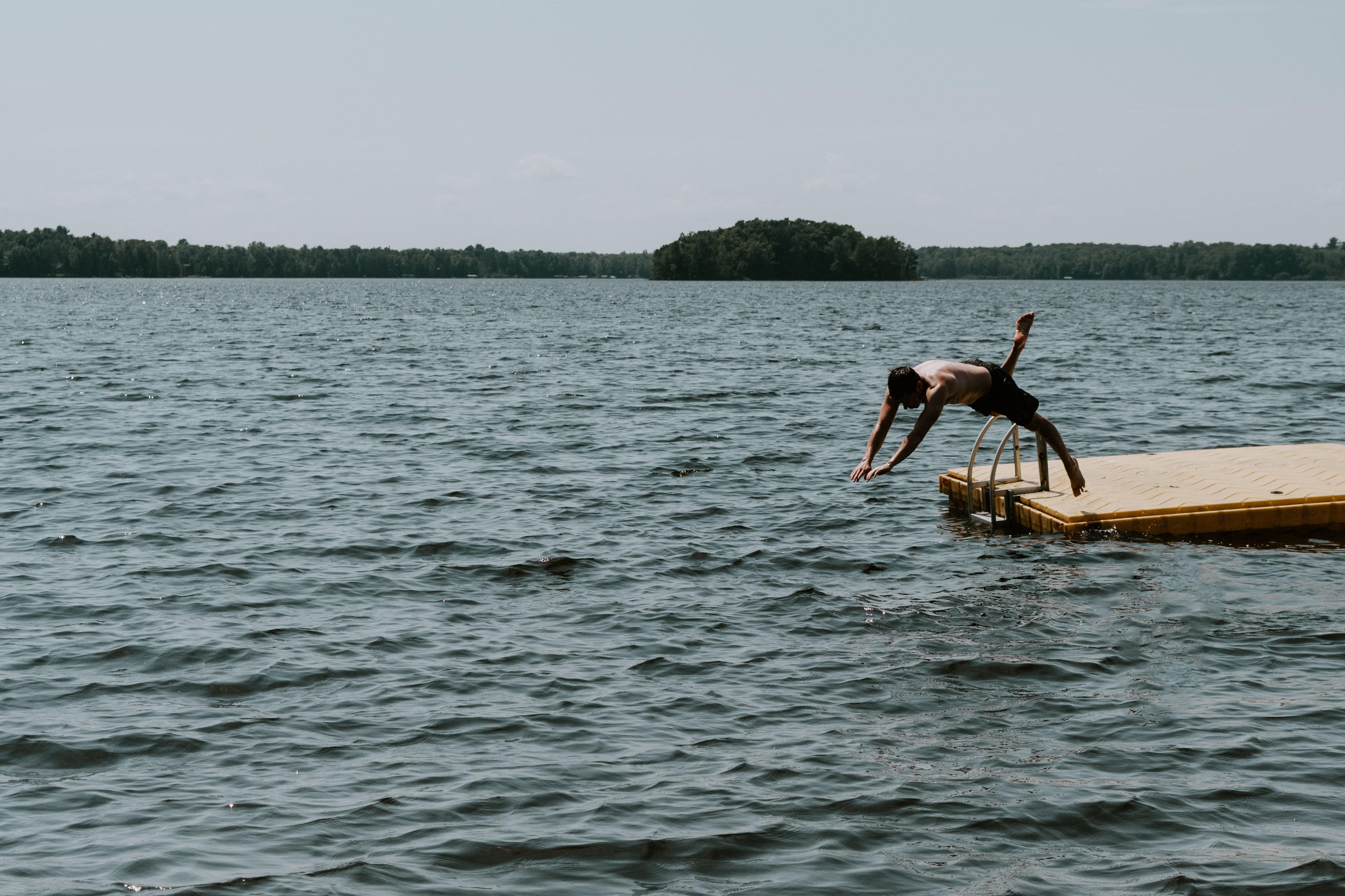 man diving on large body of water