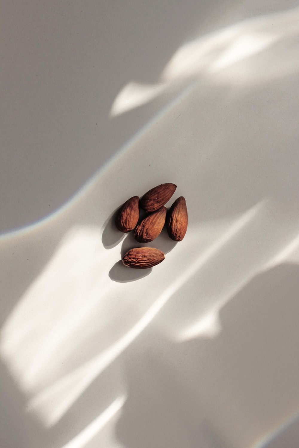 close-up of almond nuts on white surface