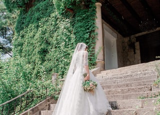 bride walking on stairway near garden