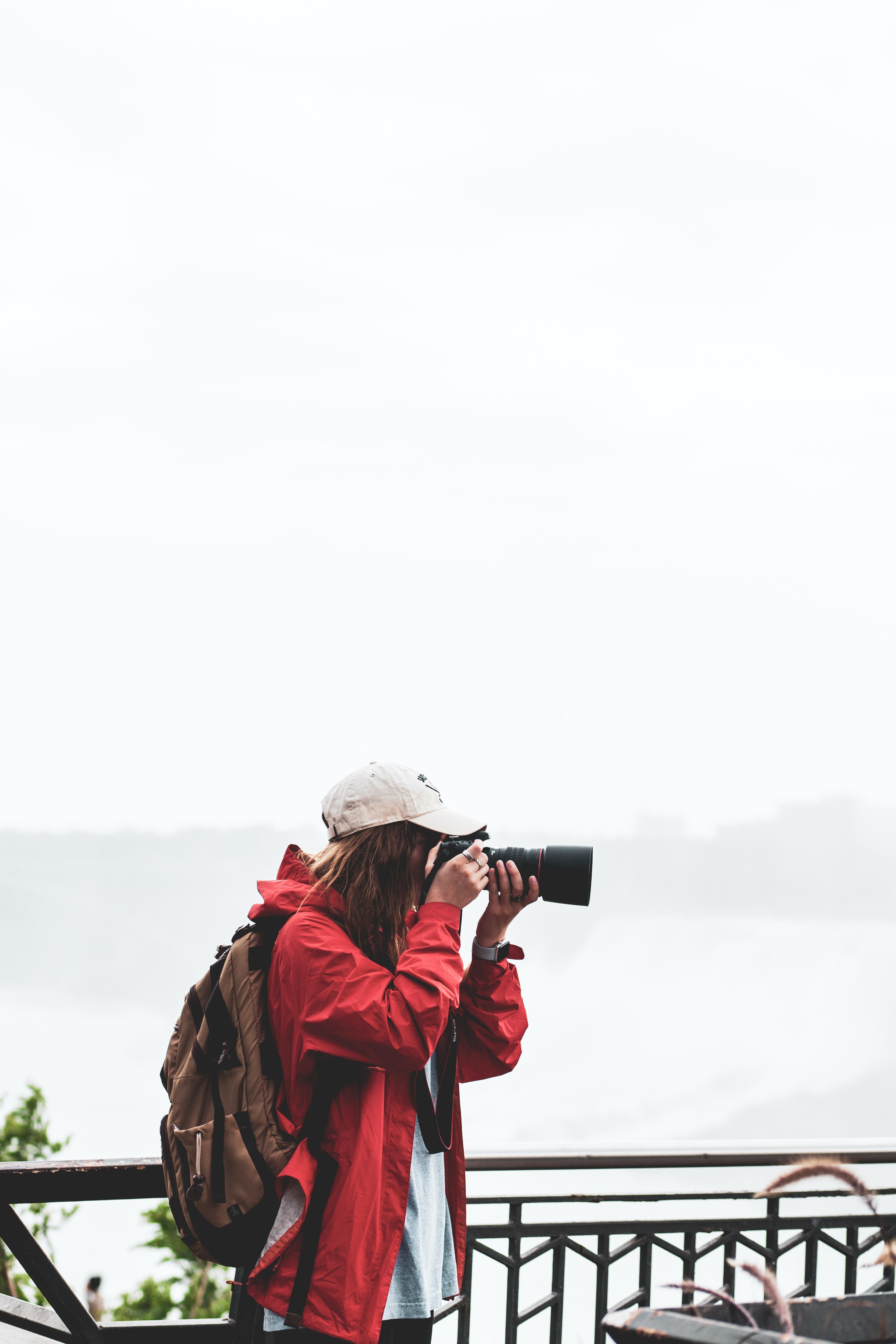 person holding black DSLR camera taking camera shot during daytime