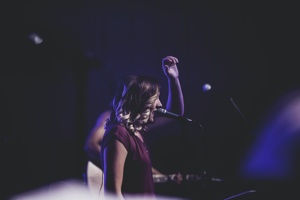 woman singing using microphone on stage