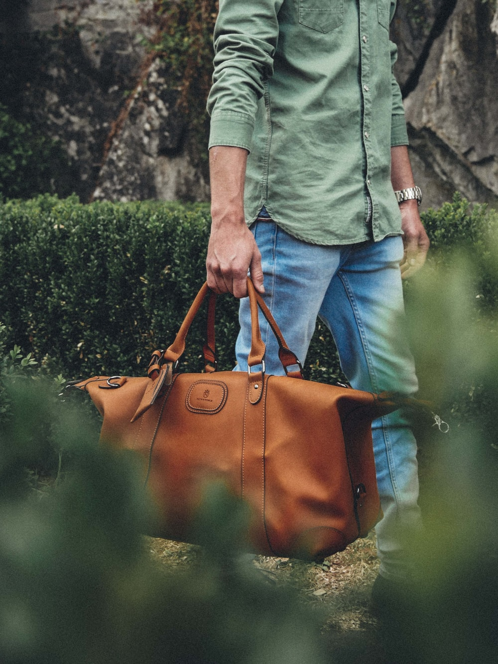 man holding bag near grass
