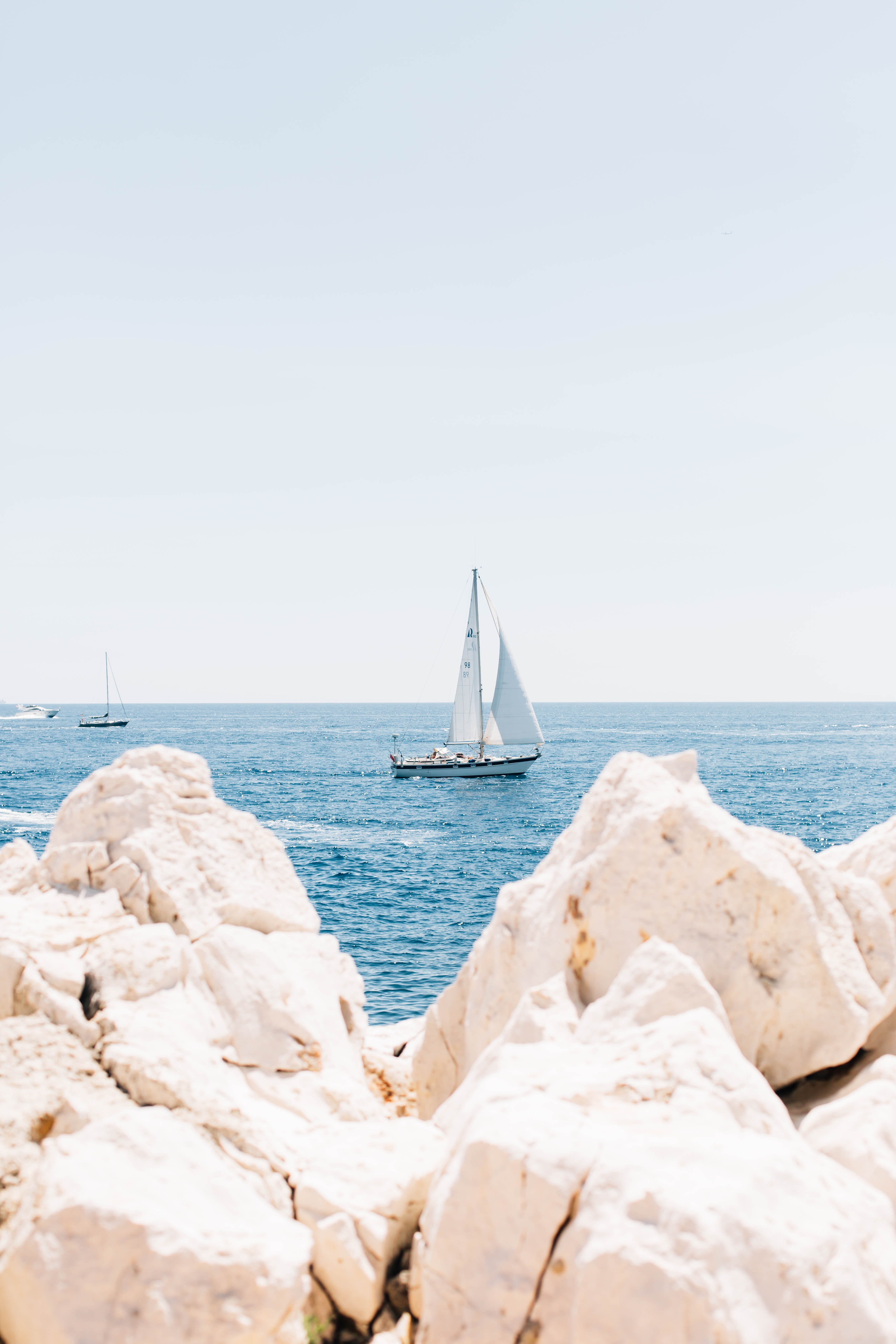 white sail boat on body of water