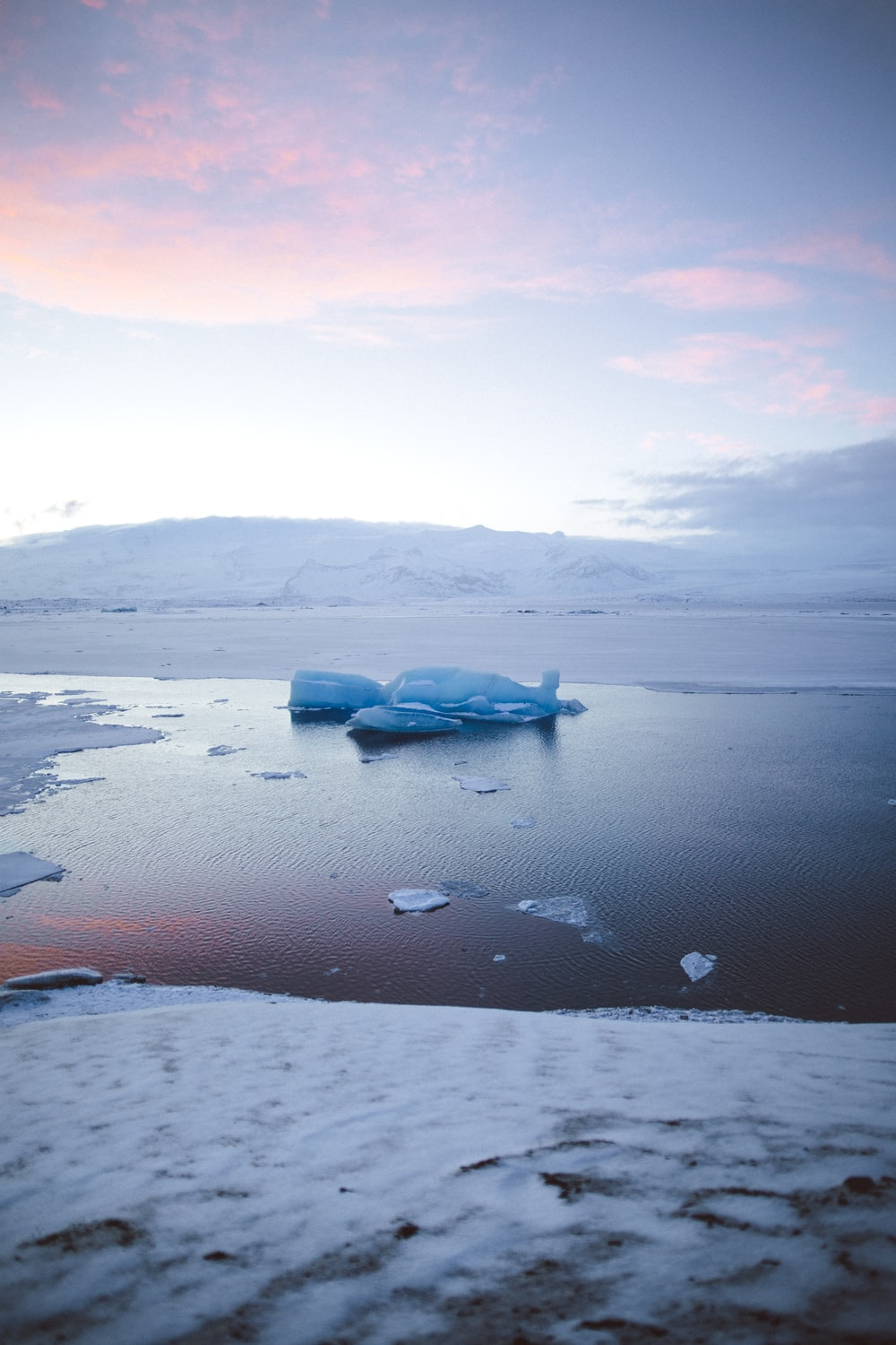 iceberg floating on water under blue and pink sky