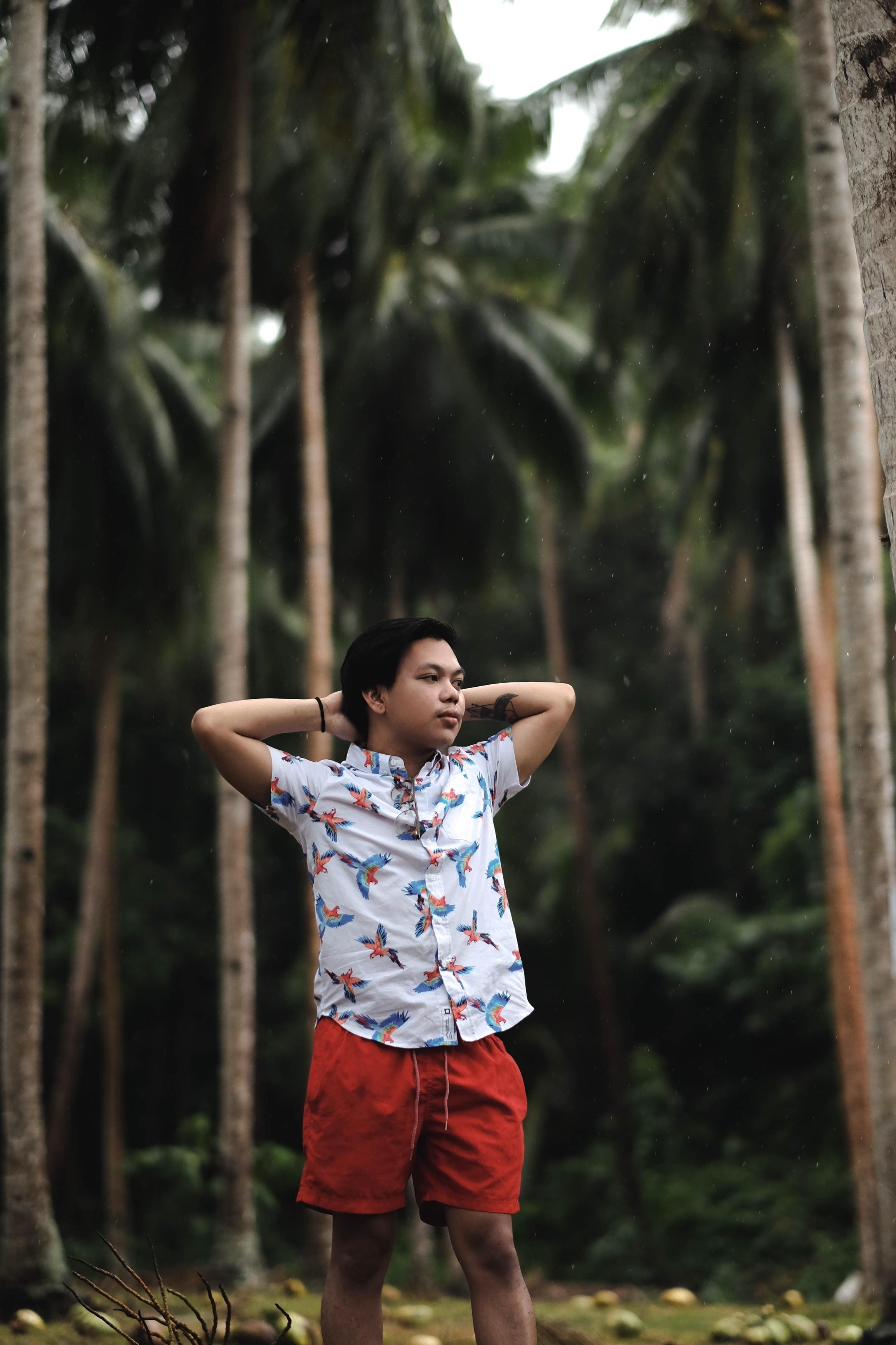 boy standing near trees