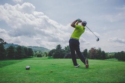 photo of man swinging golf driver golf teams background