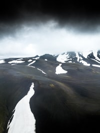 snow capped mountain under dark clouds