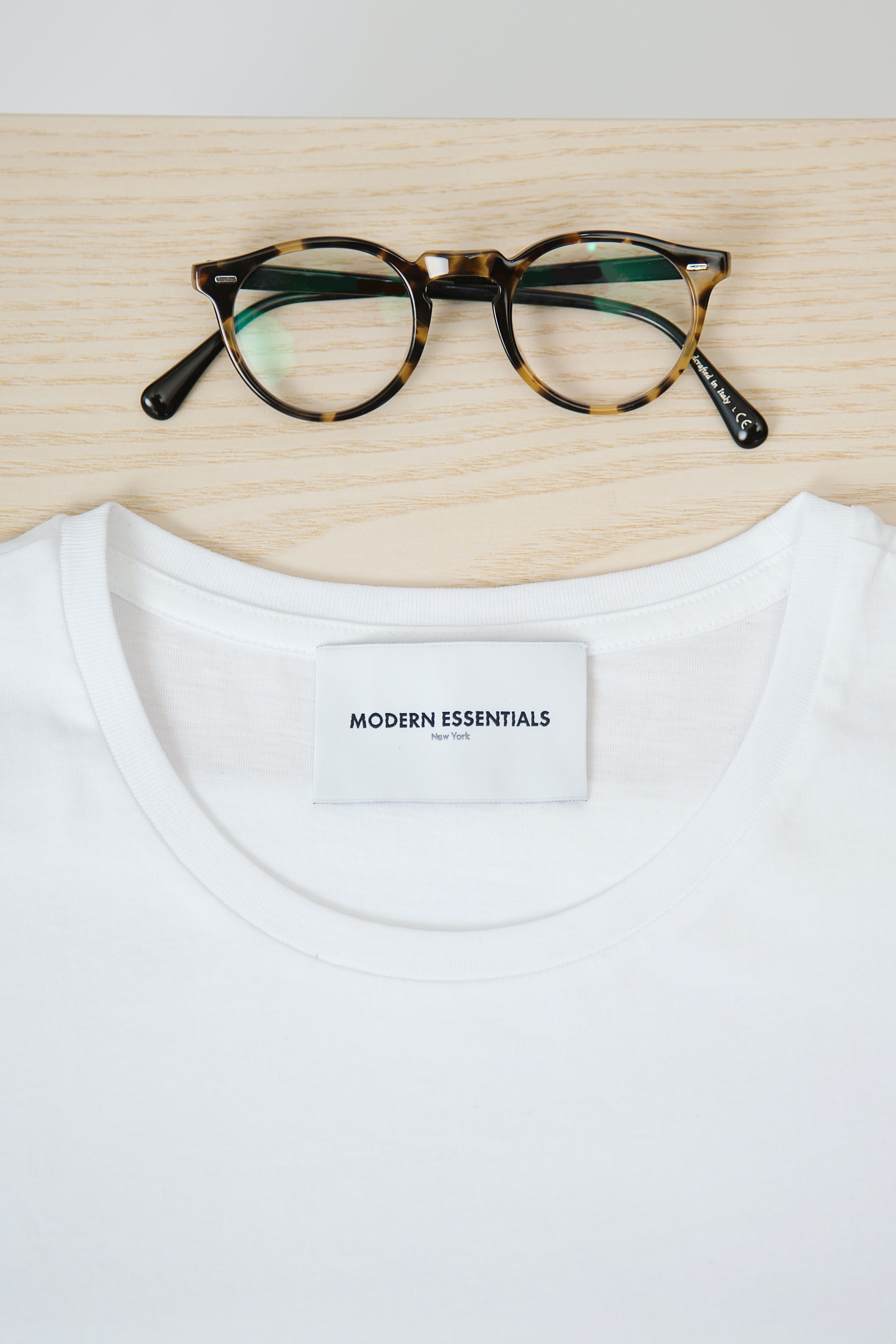 close-up photography of white Modern Essentials crew-neck shirt and black and brown framed eyeglasses on brown slab