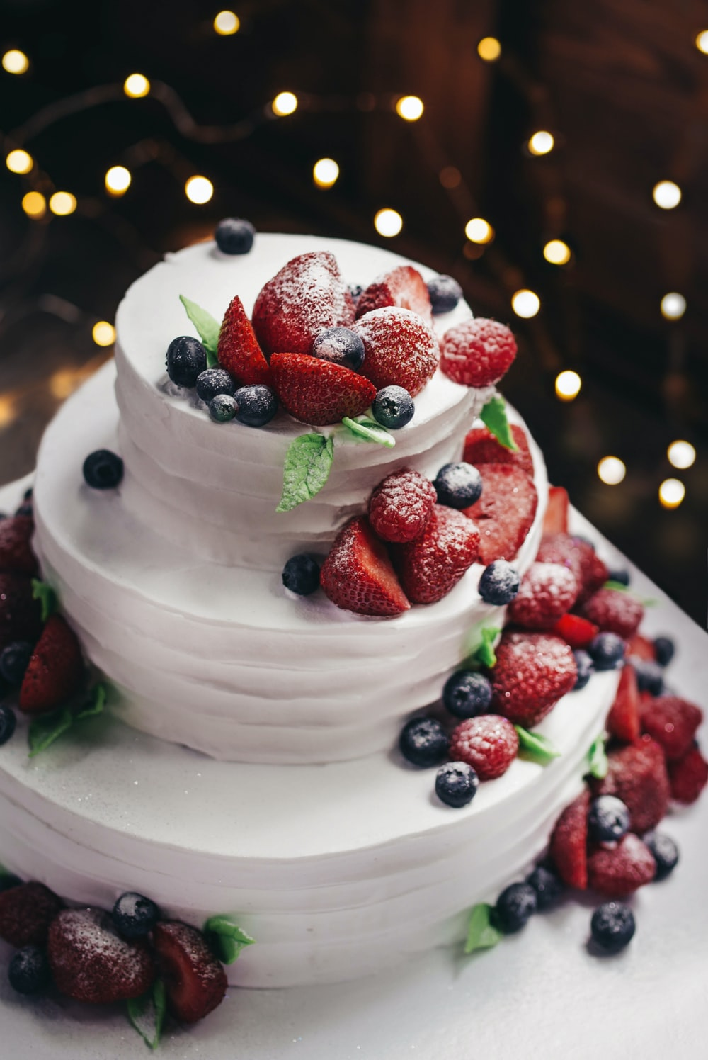 close-up photography of 3-tier vanilla cake with blueberry and strawberry toppings