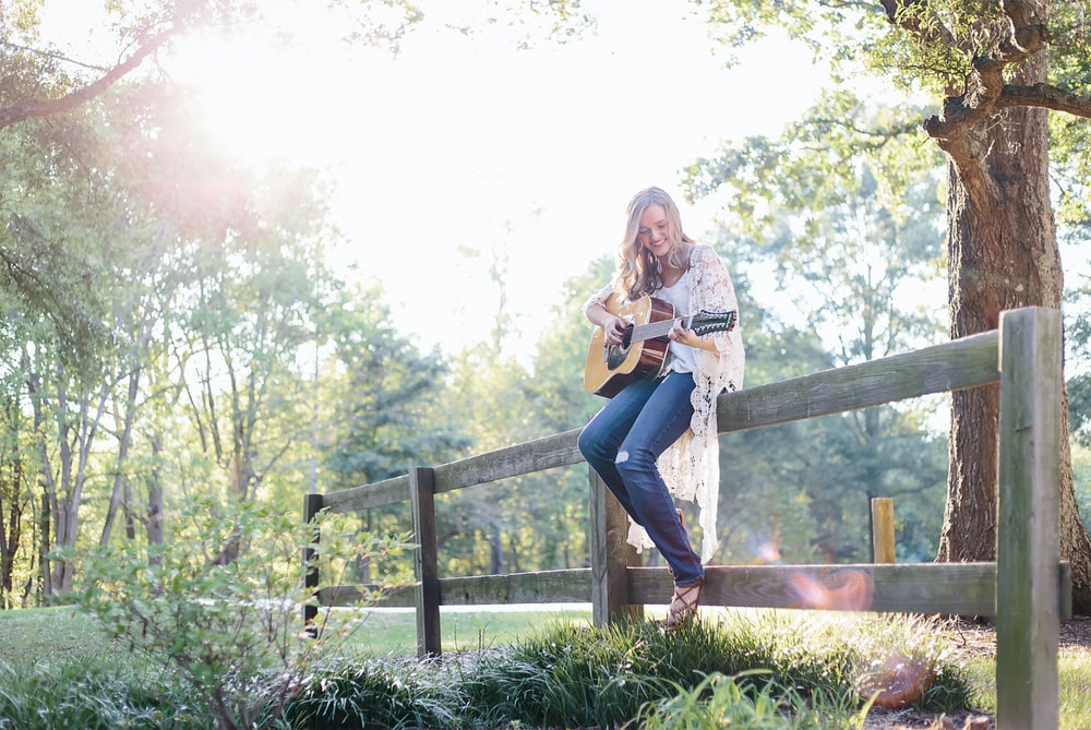 woman sitting on fence while playing guitar