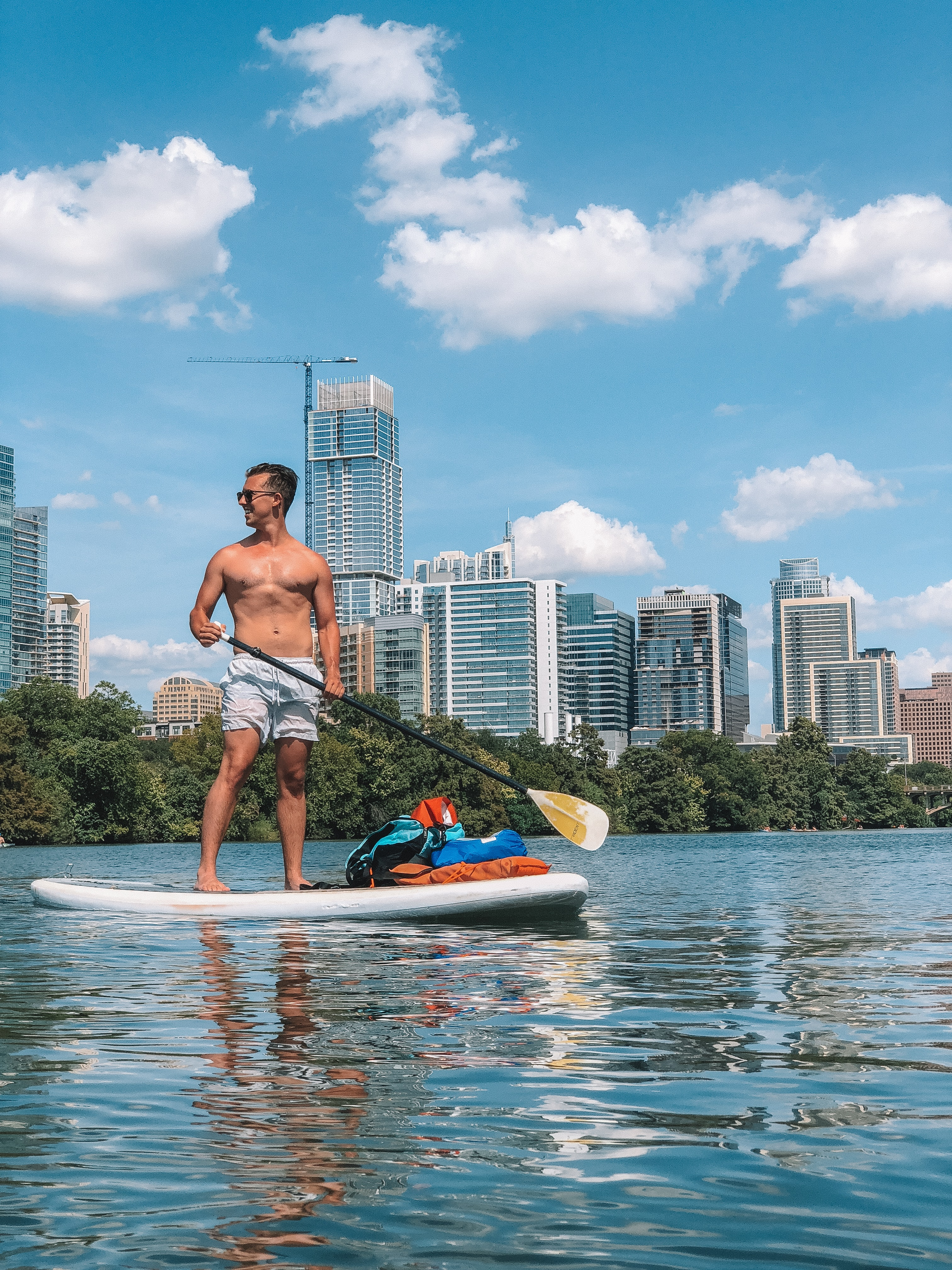 man in white shorts on paddle board