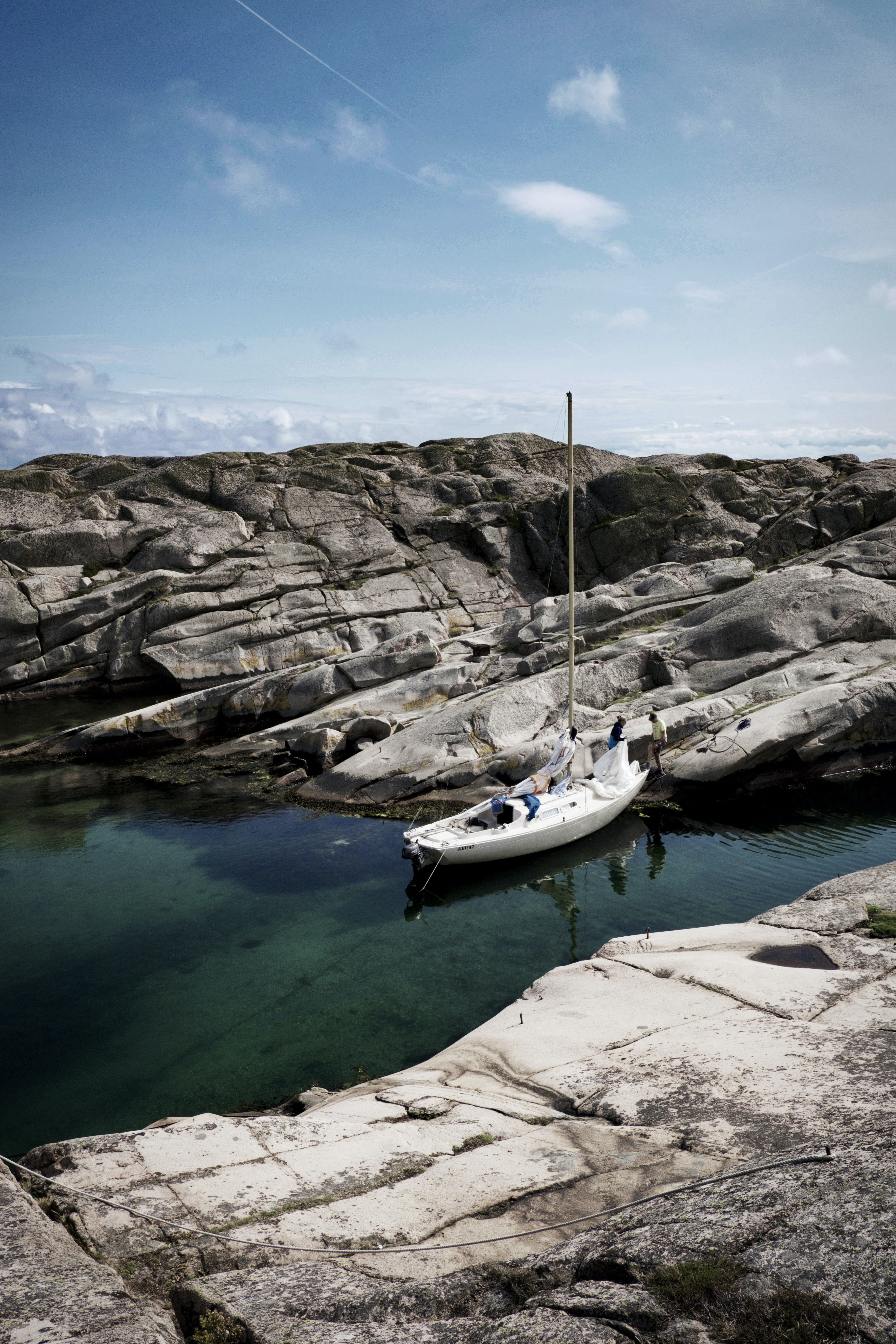 white boat on water beside rock formation