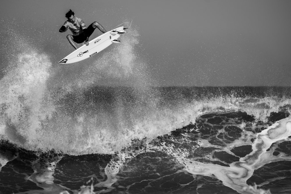 grayscale man surfing