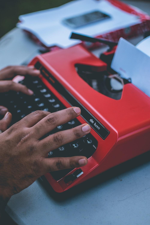 person typing on red typewriter