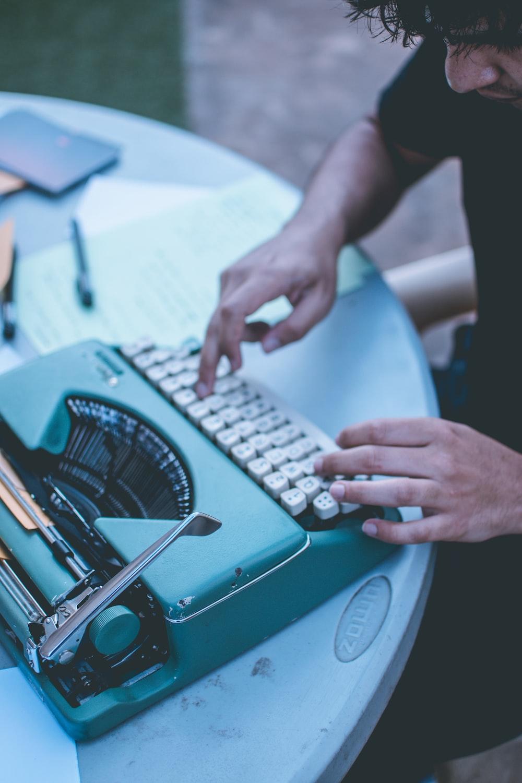 man using gray and white typewriter