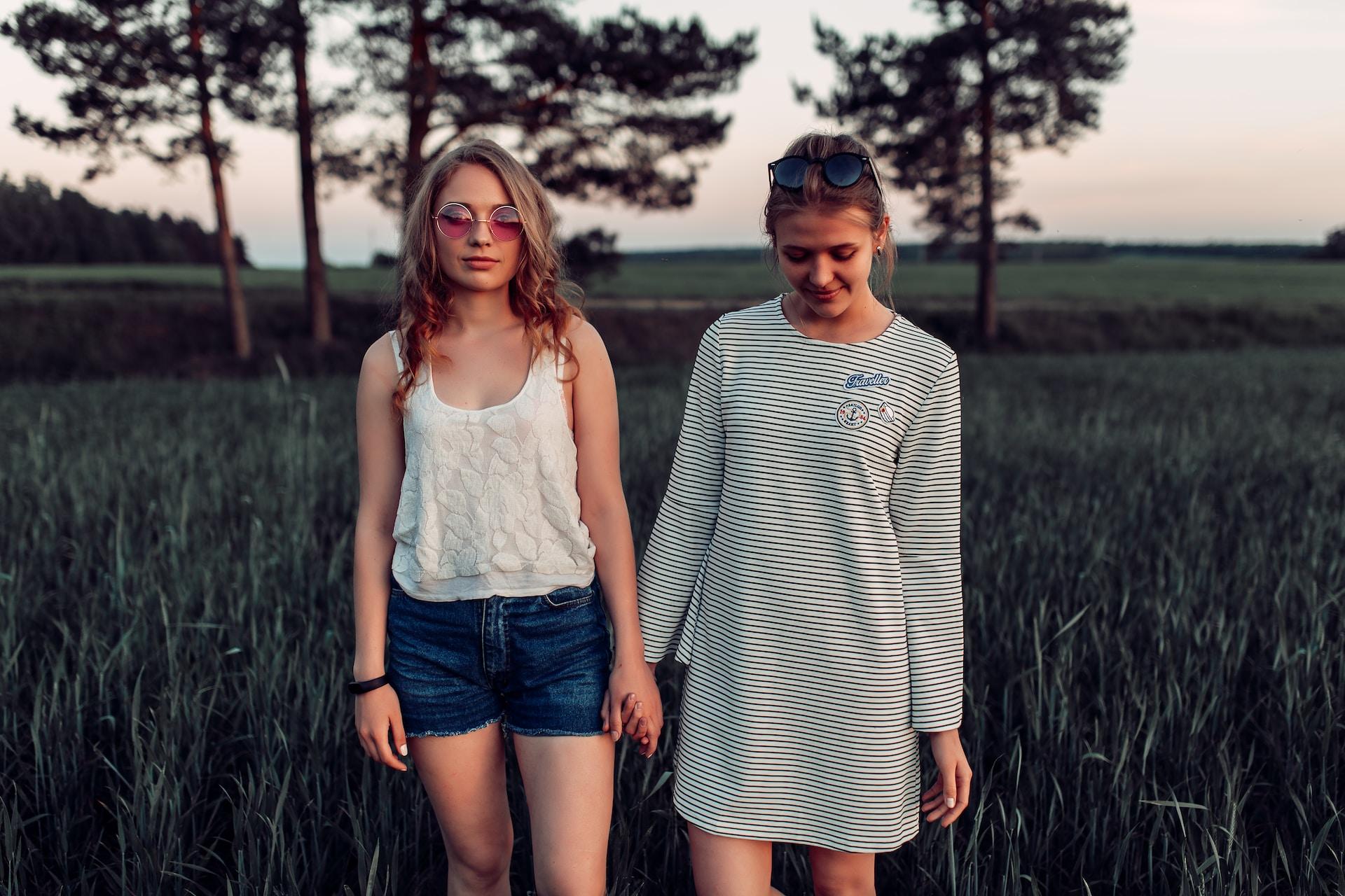 two woman walking on grass land
