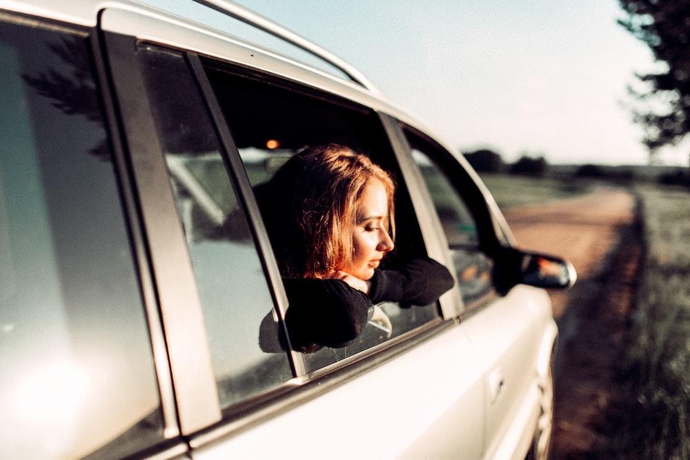 woman riding silver car