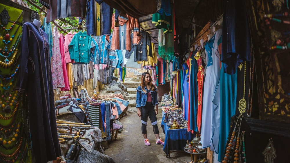 woman surrounded by assorted color apparel