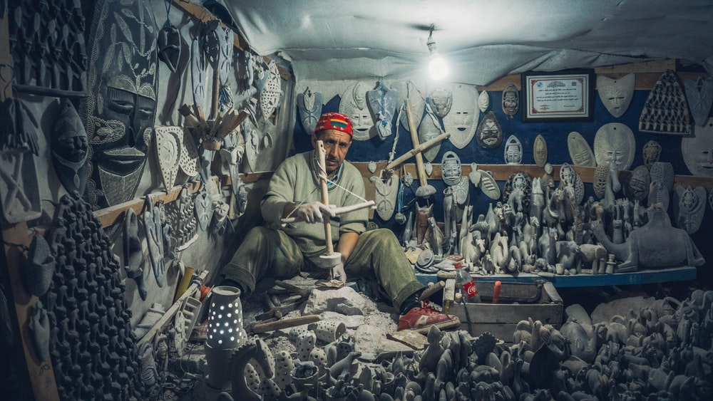 man making statue in house