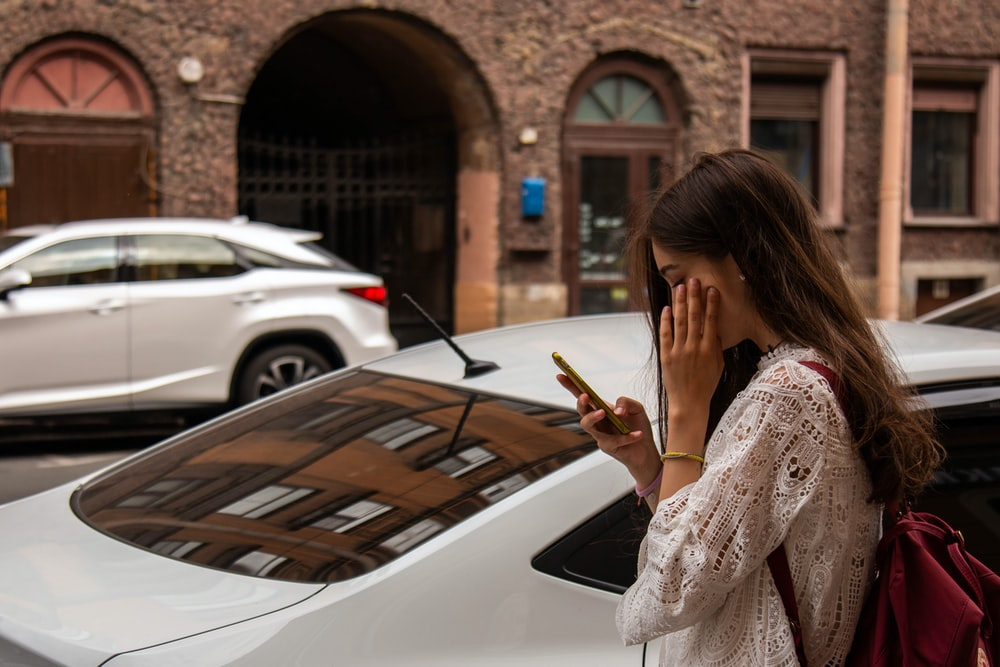 woman wearing white blouse beside white vehicle