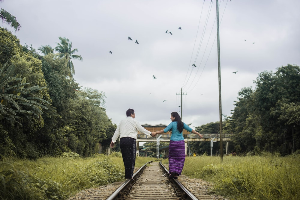 woman and man holding hands while walking on train tracks