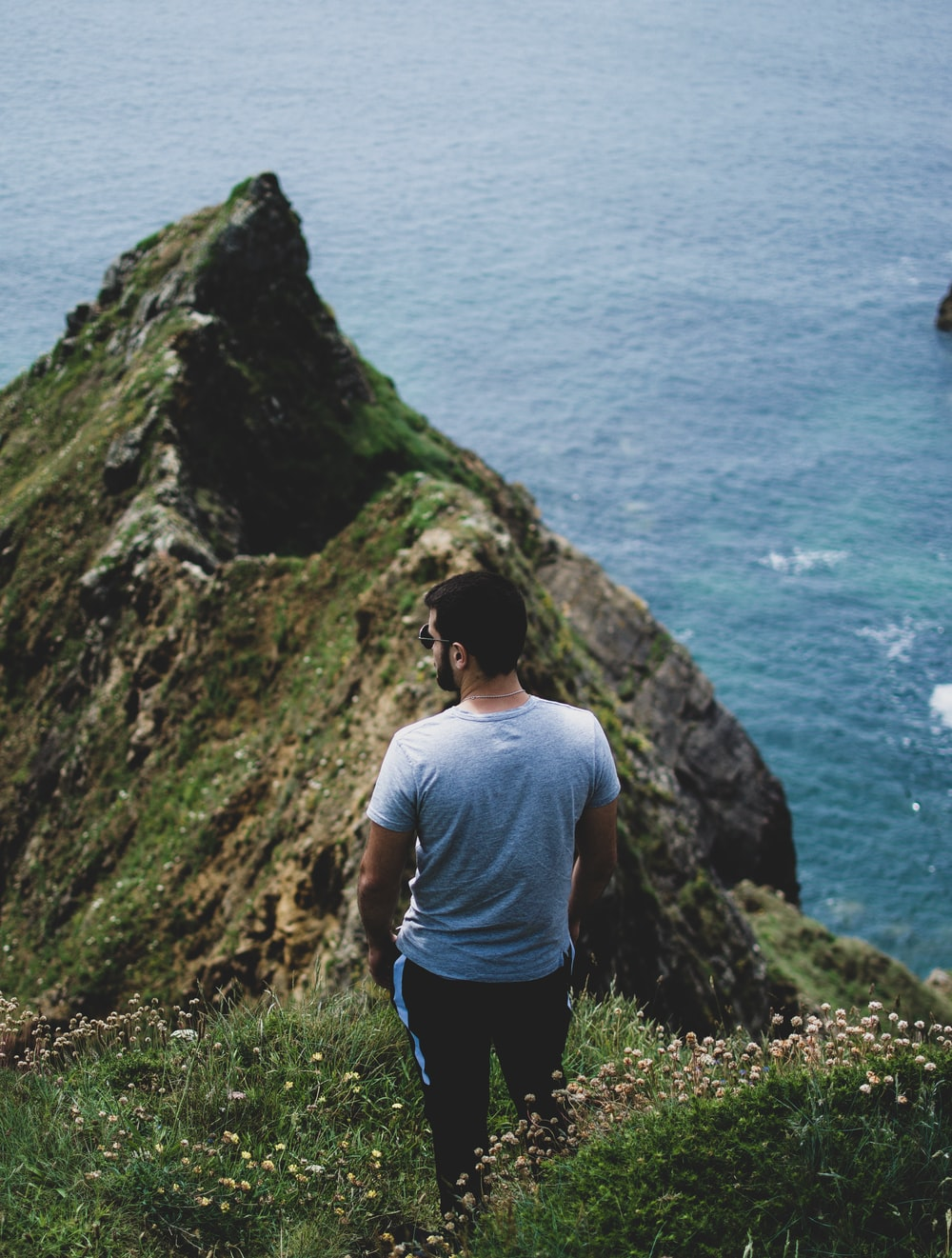 man standing near cliff while facing body of water at daytime