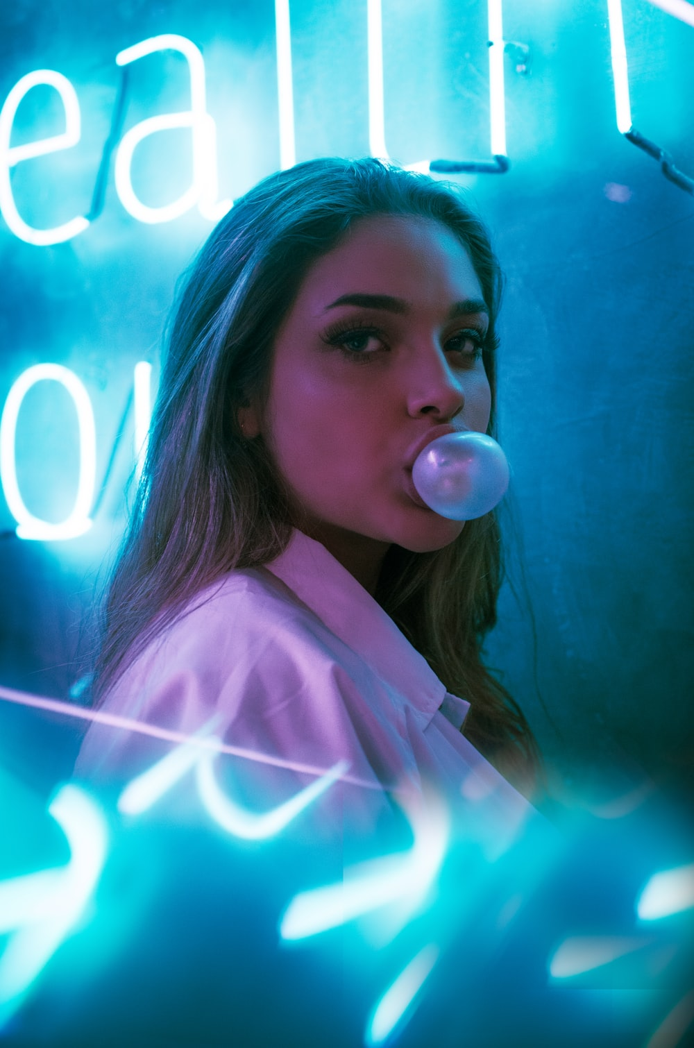 selective focus photo of woman blowing gum standing in front of turned-on neon signage