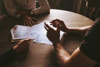 丸テーブルを囲んでマーケティングについて会議をしている3人