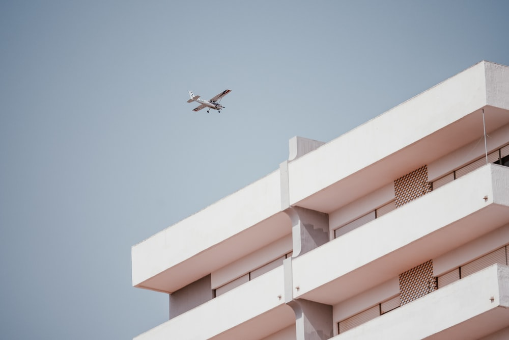 white monoplane passing thru building