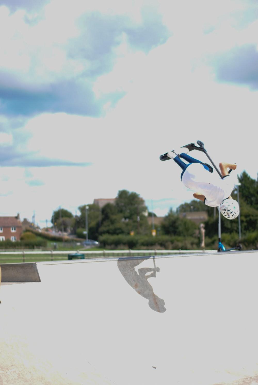 person in white t-shirt skateboarding at the skate park