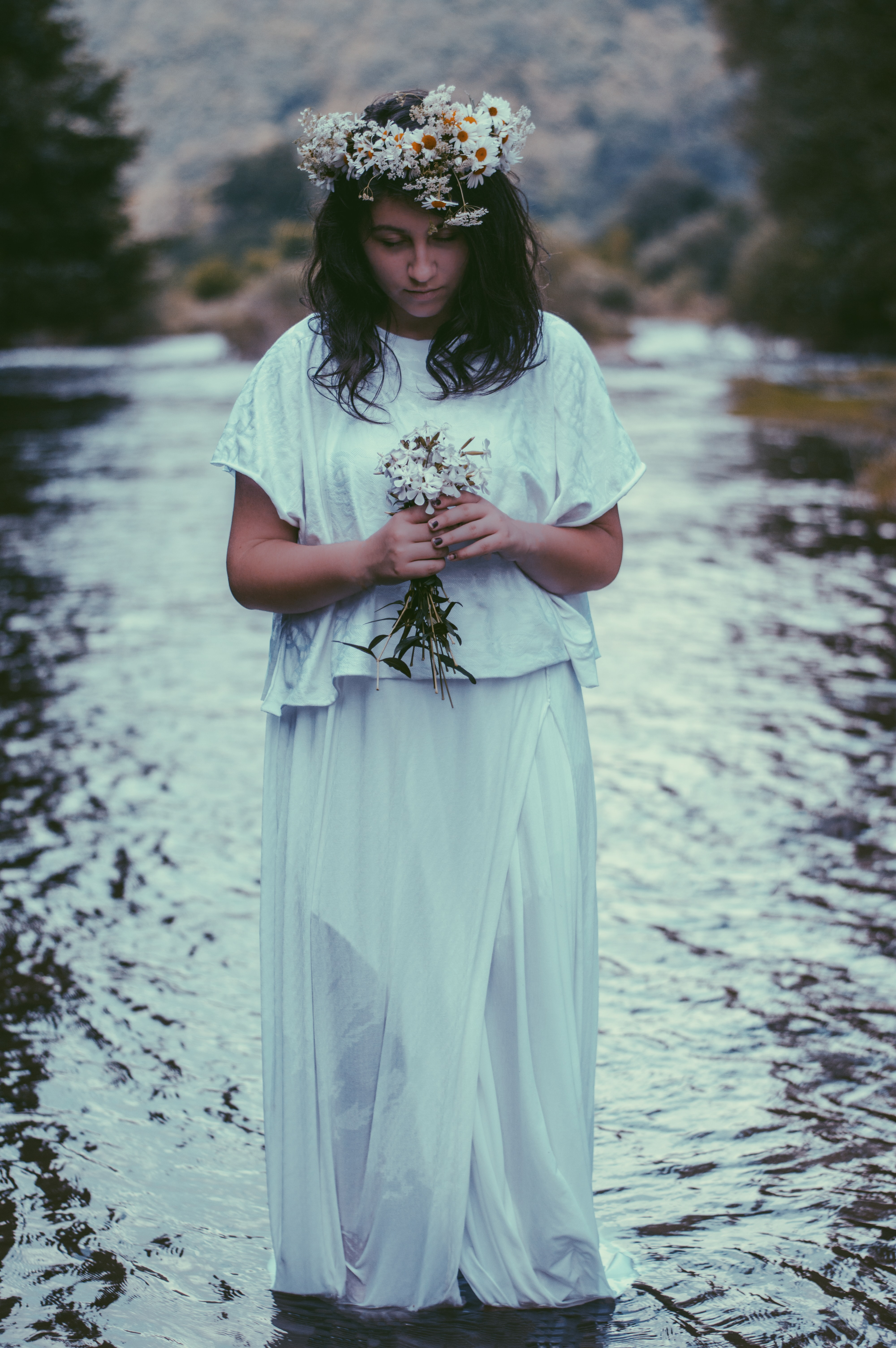woman wearing dress and holding flower standing in body of water