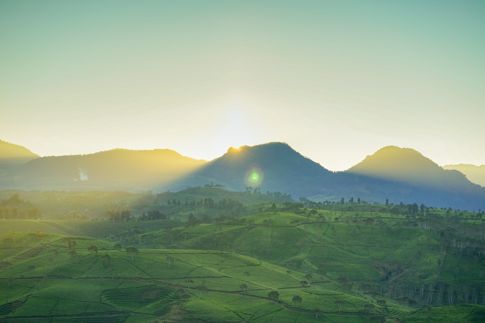 landscape photo of green field and mountains during daytime