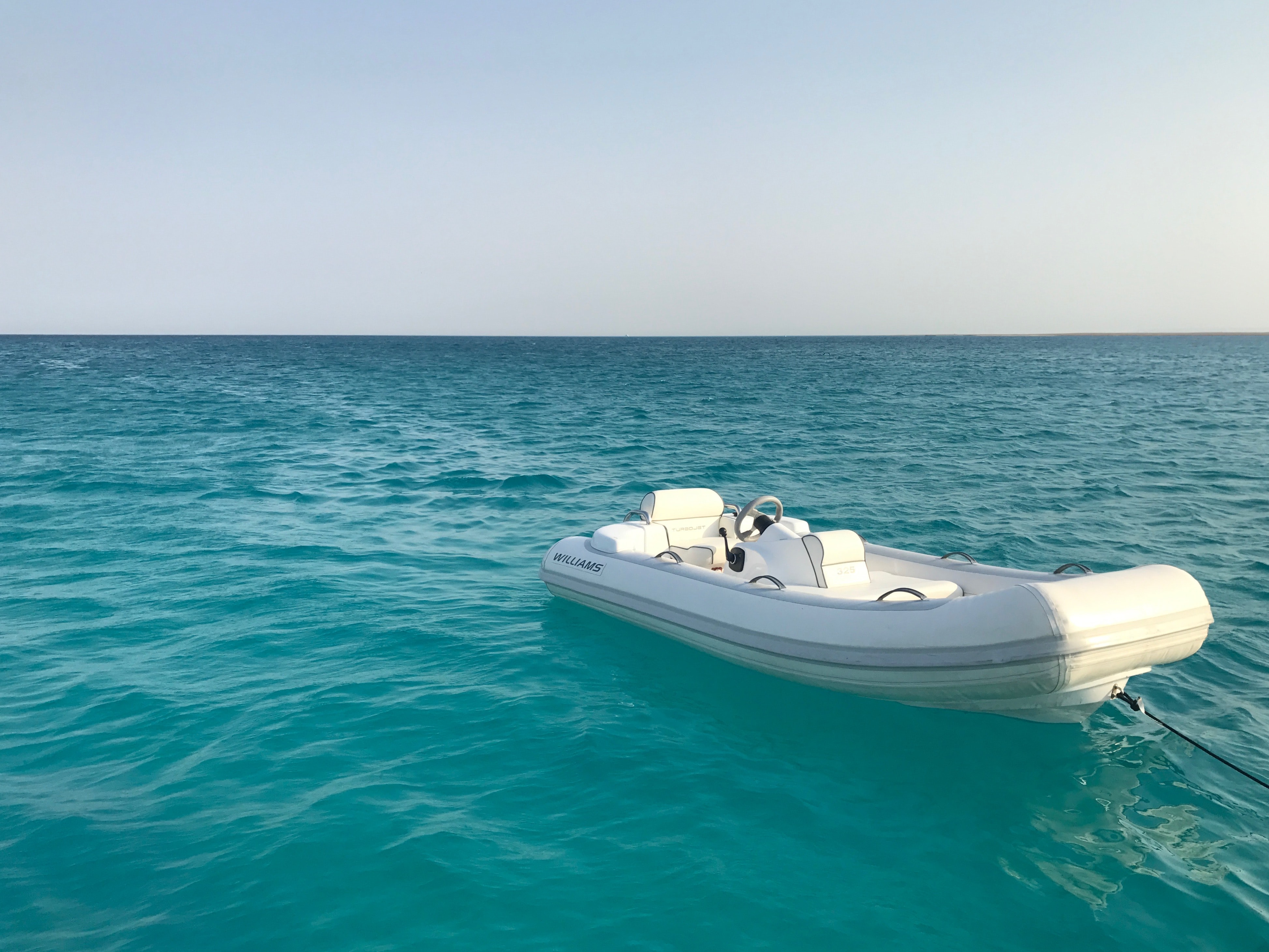 white boat floating on body of water