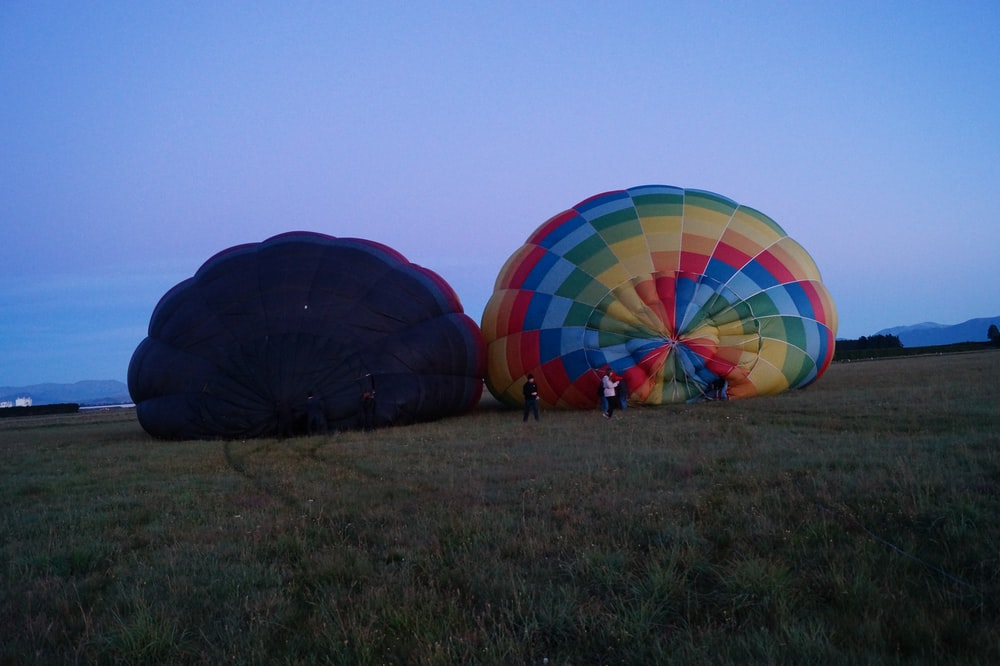 two hot air balloons on grass field