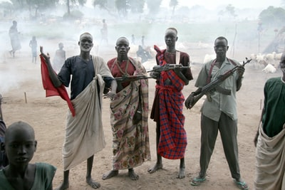 four men holding assault rifles south sudan teams background