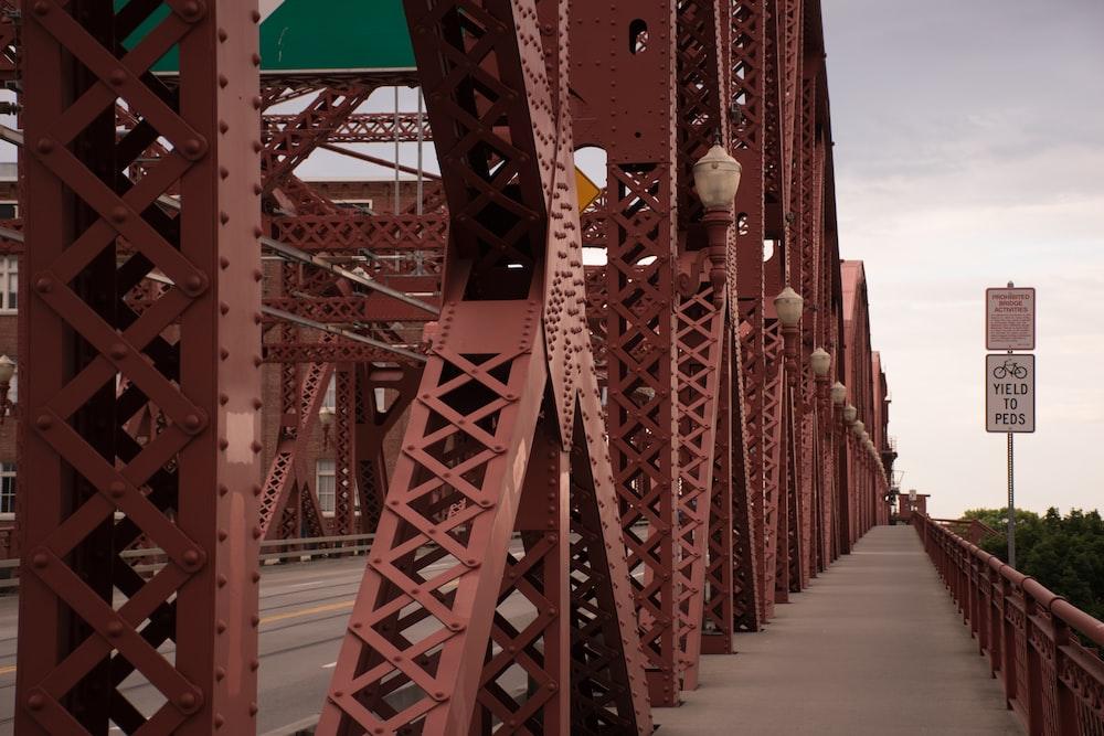 white signage mounted on bridge side walk