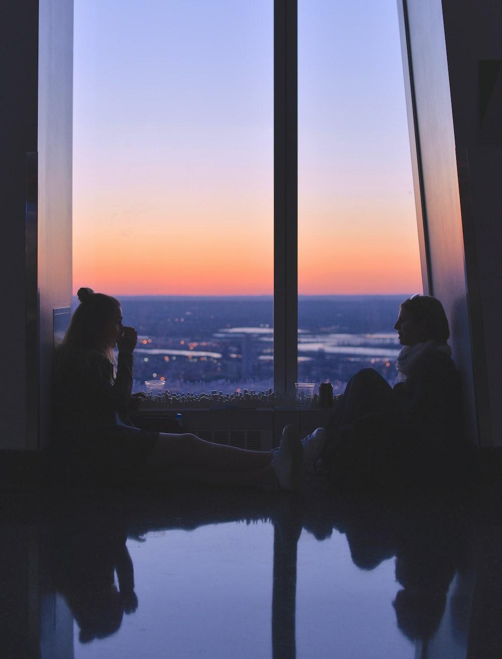 two women sitting near window