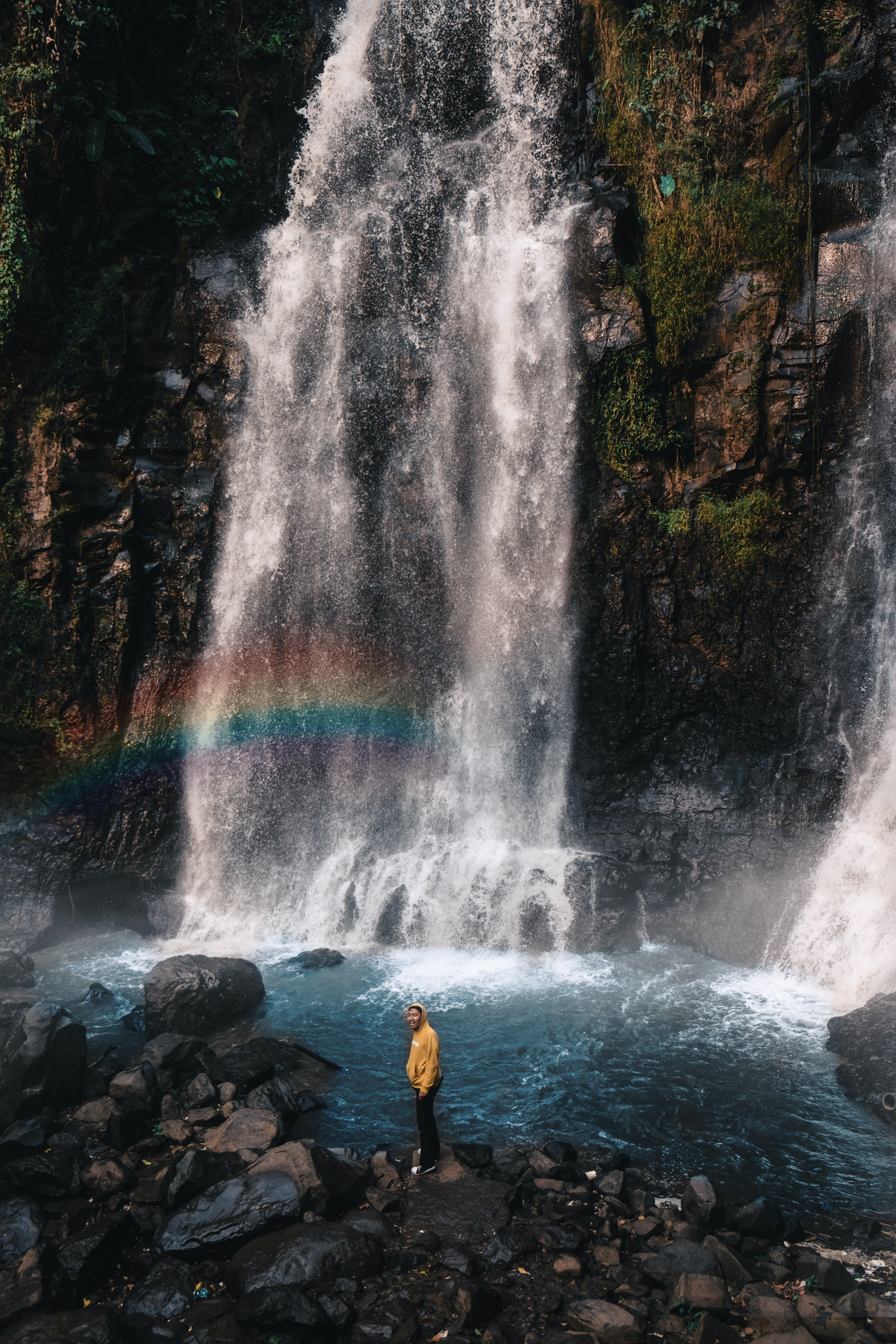 man standing on rock near waterfalls